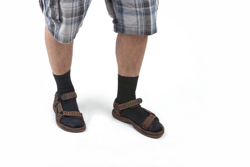 studio shot of a man wearing sandals with socks and having hairy legs, isolated on white.